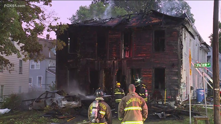 One killed after car slams into Manchester home, catching fire
